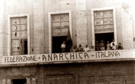 Casal de la FAI de Messina en los locales ocupados del Palazzo Littorio.  Gino Cerrito es el primero por la izquierda, derecho, junto a la bandera  (Messina, 28 de agosto de 1947)
